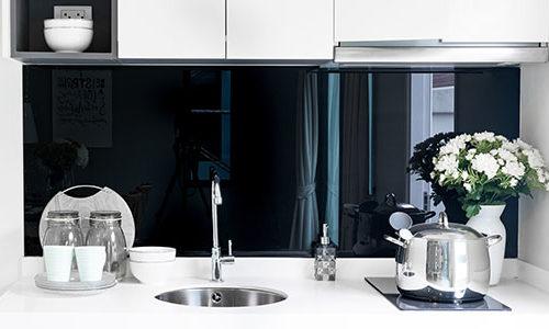 Svart glassplate over hvit kjøkkenbenk