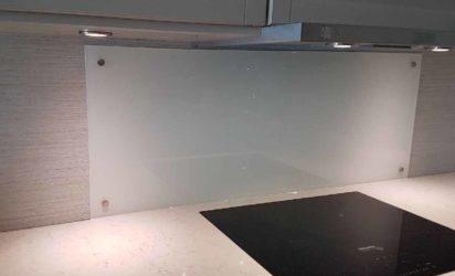 Glassplate bak komfyr festet med pynteskruer