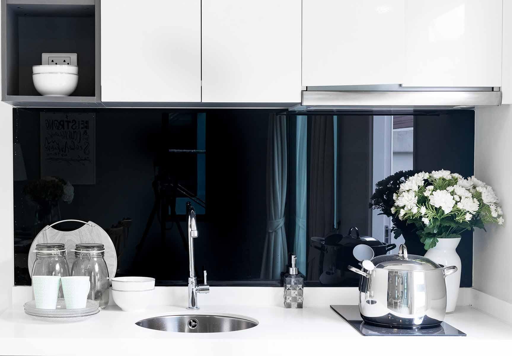 Svart glassplate på hvitt kjøkken