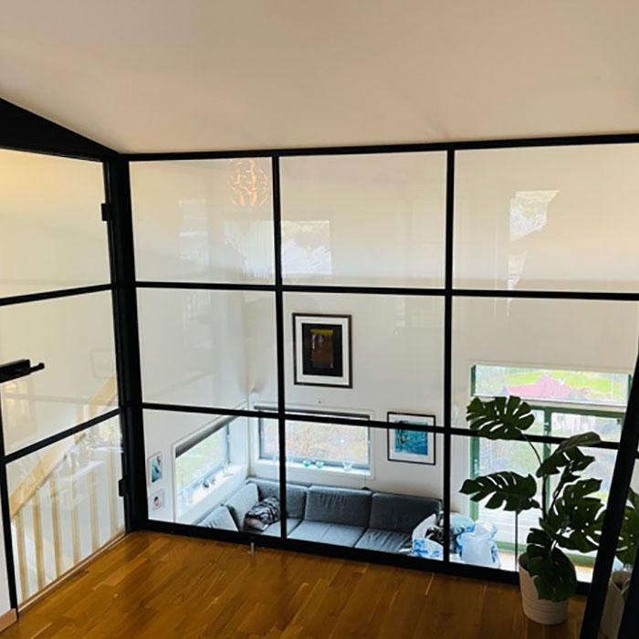 glassvegger med svarte sprosser mot trapp