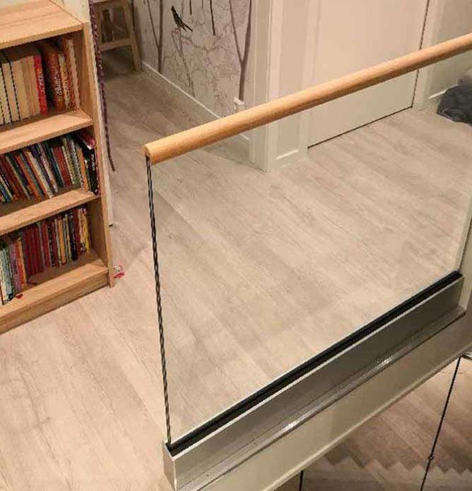 Glassrekkverk irundt trapp med håndløper i tre