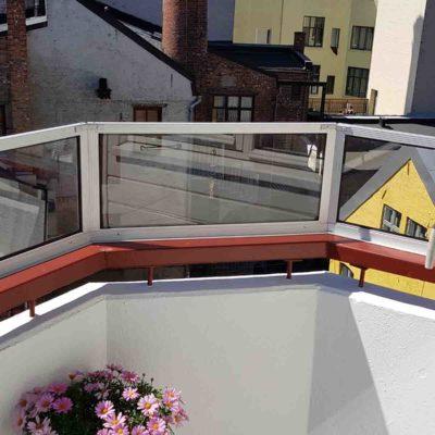 Skjermvegg i glass som forlenger av rekkverk rundt balkong