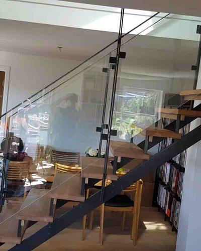 Glassrekkverk i trapp med håndløper i stål