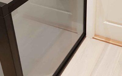 Glassrekkverk med svart ramme montert i trapp