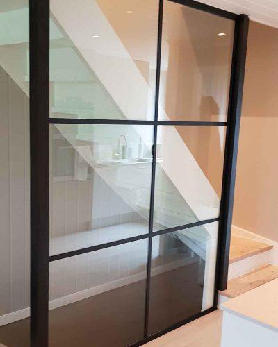 Glassvegger med svarte sprosser montert i trapp