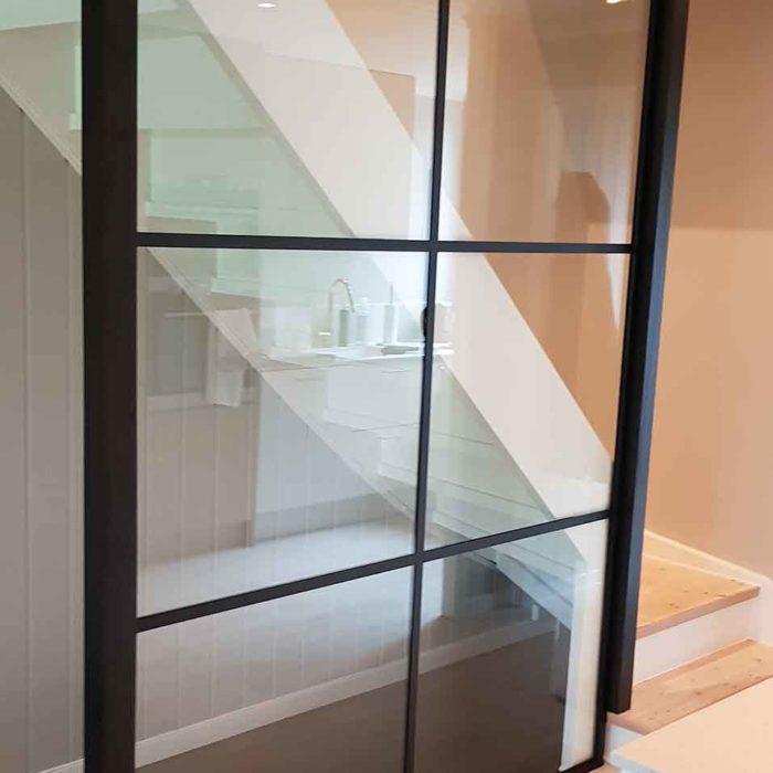 Glassvegg med svarte sprosser montert i trapp