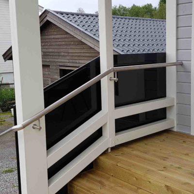 Svart glassvegg fungerer som glassrekkverk til trapp ute