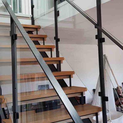 Glassrekkverk og glassvegg i trapp med håndløper i stål