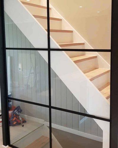 Glassvegg med svarte sprosser mot trapp