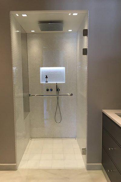 Dusjnisje med dusjdør med bøylehåndtak