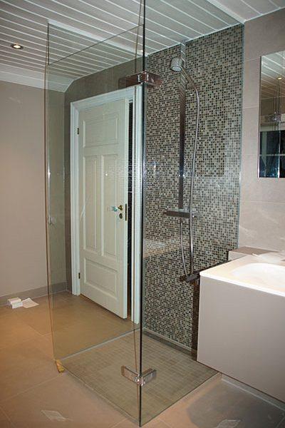 Frittstående dusjhjørne med dusjvegger og dusjdør plassert midt i rommet