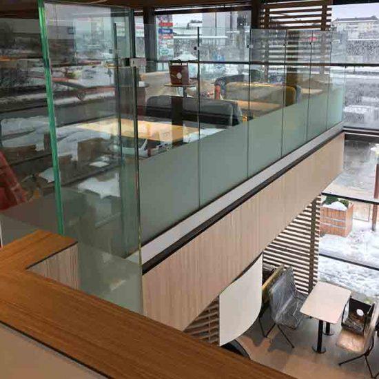 Glassrekkverk i og rundt trapp inne hos Mc. Donalds