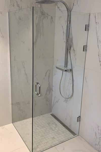 Dusjhjørne med en dusjvegg og en dusjdør i herdet glass