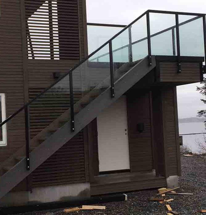 glassrekkverk med svarte stolper og håndløper til trapp ute