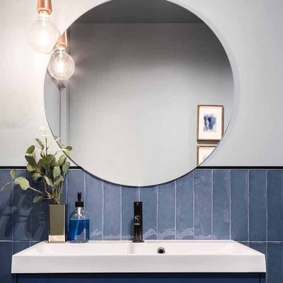 stort rundt speil over vasken på badet