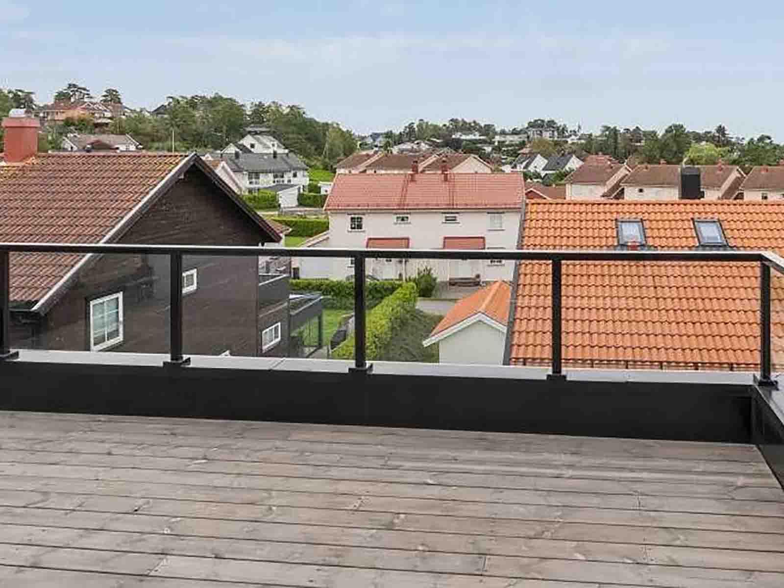 glassrekkverk med svarte stolper og håndløper til takterrasse