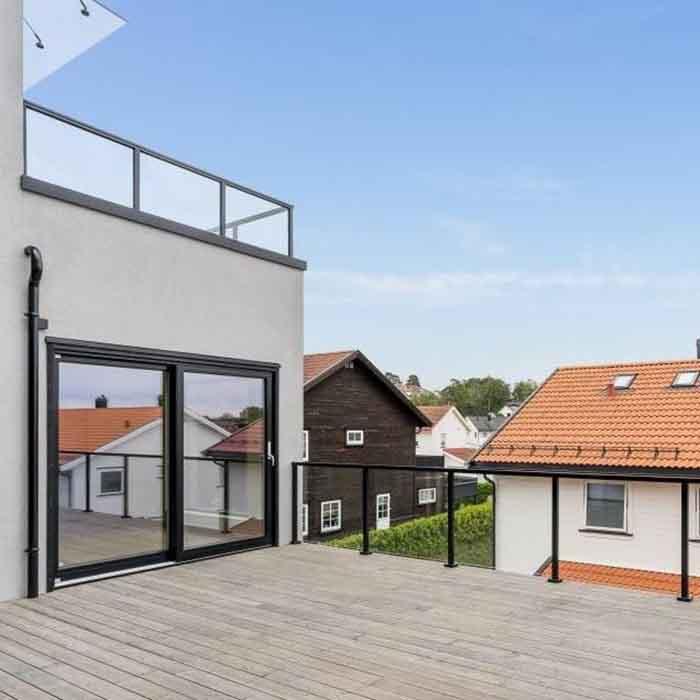 glassrekkverk med svarte stolper og håndløper til terrasse