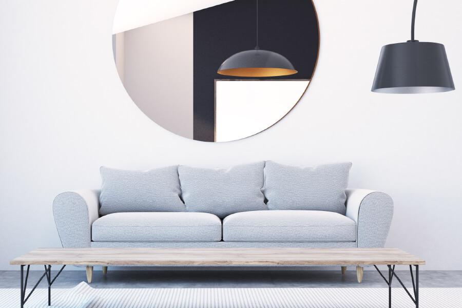 stort rundt speil over sofa i stue