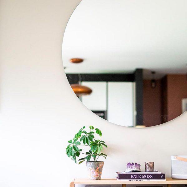 stort rundt speil festet på vegg med usynlige fester