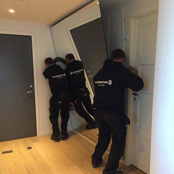 glassmester1 montører i ferd med å feste speil på vegg for kunde