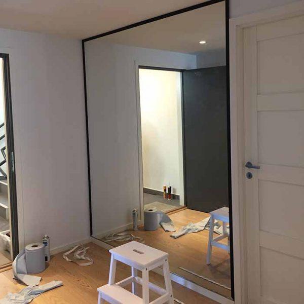 glassmester1 montører ferdig med å feste speil på vegg for kunde
