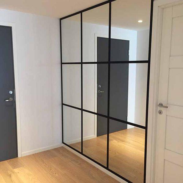 glassmester1 ferdig med å feste speil på vegg for kunde