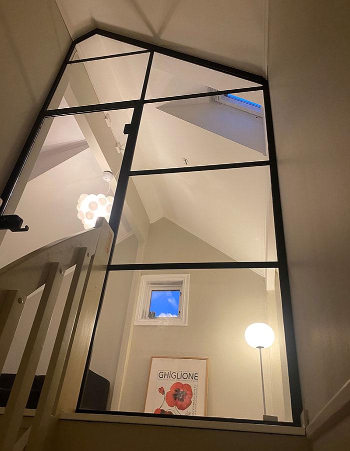 glassvegg og glassdør mot skråtak med svarte sprosser i den populære New York loft stilen
