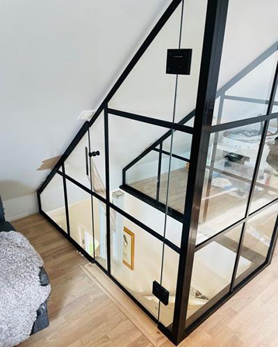 glassvegg med svarte sprosser rundt trapp