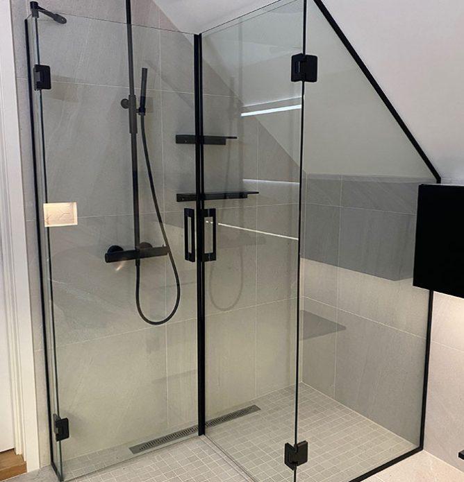 skreddersydd dusjløsning spesialtilpasset mot skråvegg og med dører som kan foldes inn for maksimal utnyttelse av plassen