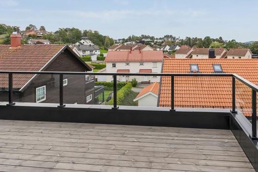 glassrekkverk med svarte stolper og rekkverk på terrasse