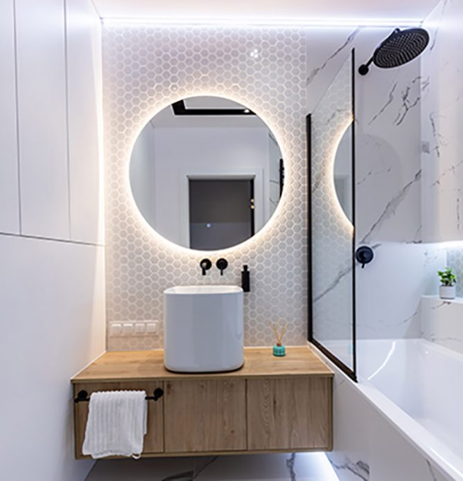 badekarvegg med svarte profiler og stort rundt speil på badet