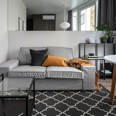 Interior in a modern style with white walls, parquet and dark textured carpet. There is a gray sofa with colorful pillows and plaid, glass and wooden tables, black stand, wide mirror, plants in pots.