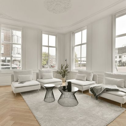 Living room with large windows, white carpet and comfortable sofas