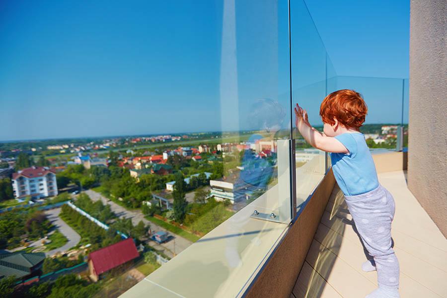 baby står og lener seg mot glassrekkverk på takterasse